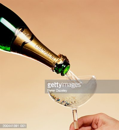 Champagne being poured into glass held by woman, close-up