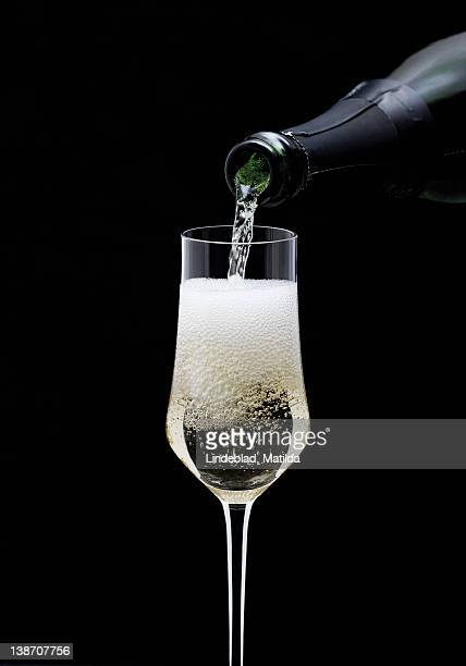 Champagne being pouring into glass from bottle, close-up