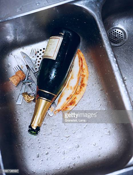Champagne bottle and cutlery in sink, close-up