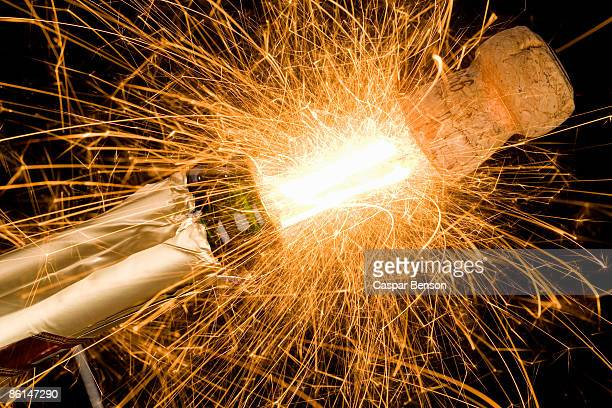 A champagne bottle opening with fireworks coming out