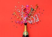 Champagne bottle with colorful party streamers on red background