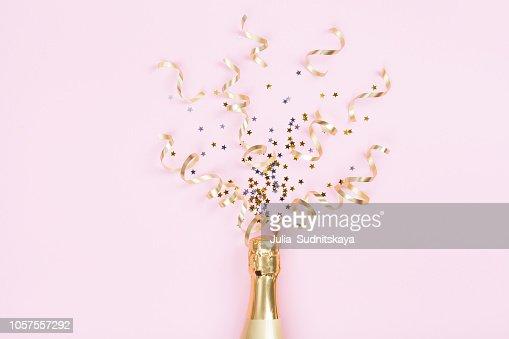 Botella de Champagne con estrellas de confeti y serpentinas de la fiesta en fondo rosa. Navidad, cumpleaños o boda concepto. La endecha plana. : Foto de stock