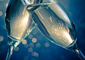 detail of champagne flutes with golden bubbles make cheers on blue light bokeh background with space for text