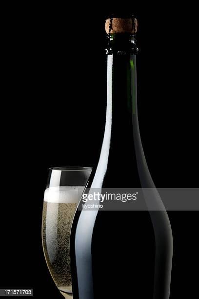 Bottiglia e bicchiere di Champagne vuote contro sfondo nero