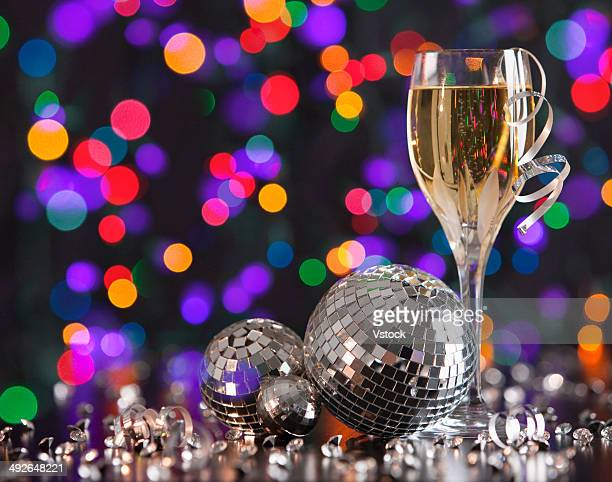 Champagne glass and disco balls on colorful background