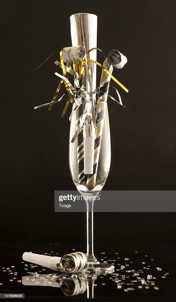 Champagne glass filled with noise makers : Stock Photo
