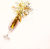 Champagne glass with golden glitter on pink background. Flatlay. Copy space. New Year concept