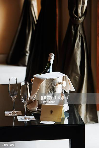Champagne glasses beside bottle in ice bucket on table