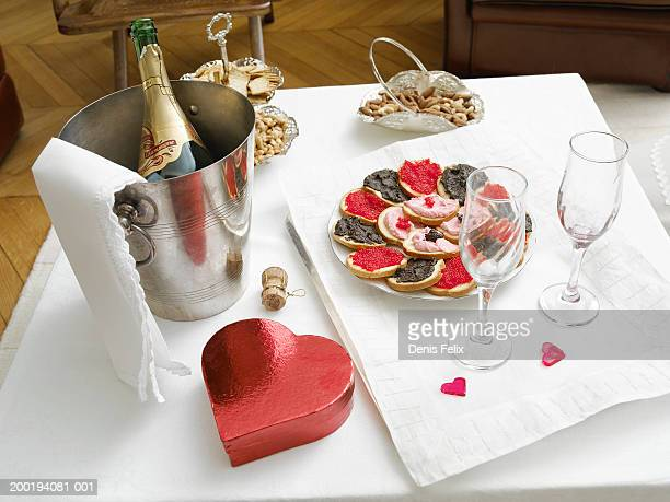 Champagne in ice bucket and luxury snacks laid out on table, close-up
