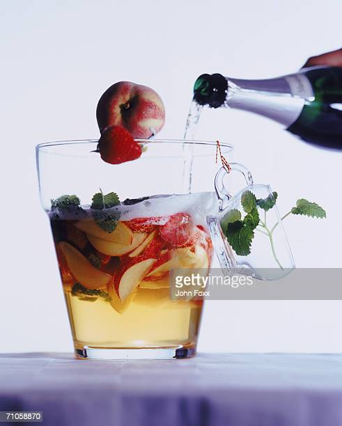 Champagne pouring into fruit slice glass, close-up
