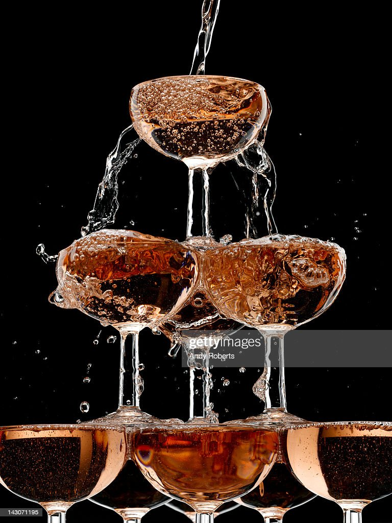 Champagne pouring into stacked glasses : Stock Photo