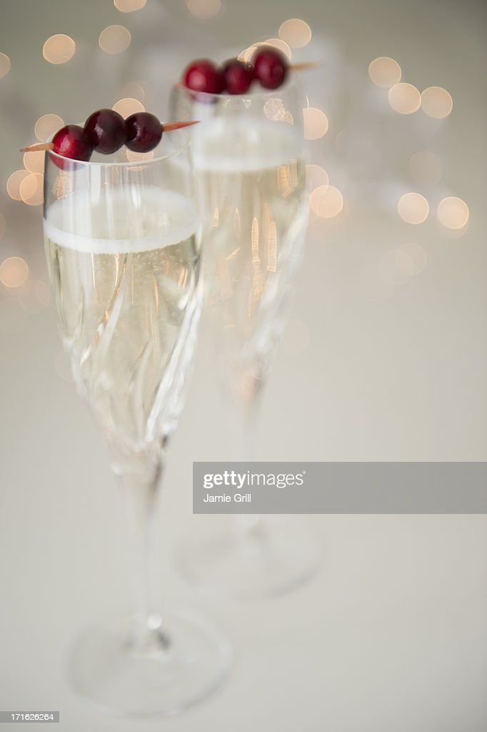 Champagne with cranberry garnish : Stock Photo