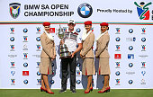 Champion Brandon Stone of South Africa poses with the South African Open trophy and Emirates airline representatives after the final round of The BMW...