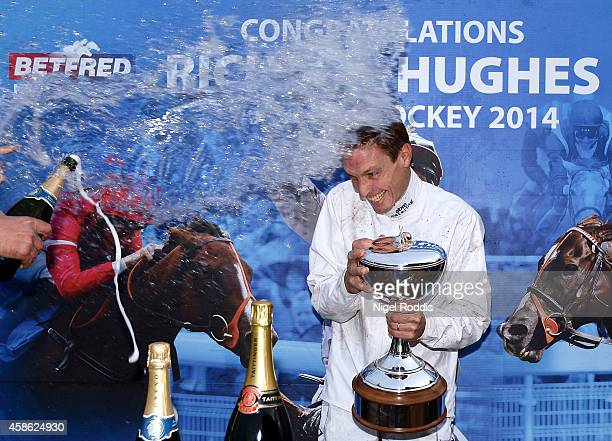 Champion jockey Richard Hughes is sprayed with water and champagne after recieving his trophy Doncaster Racecourse on November 8 2014 in Doncaster...