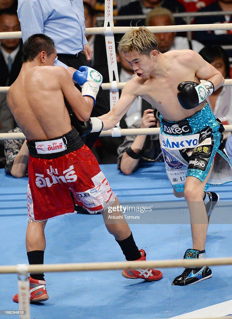 Champion Kazuto Ioka of Japan and (L) Wisanu Kokietgym of Thailand exchange punches during their WBA Light Flyweight title bout at Bodymaker Colosseum on May 8, 2013 in Osaka, Japan.