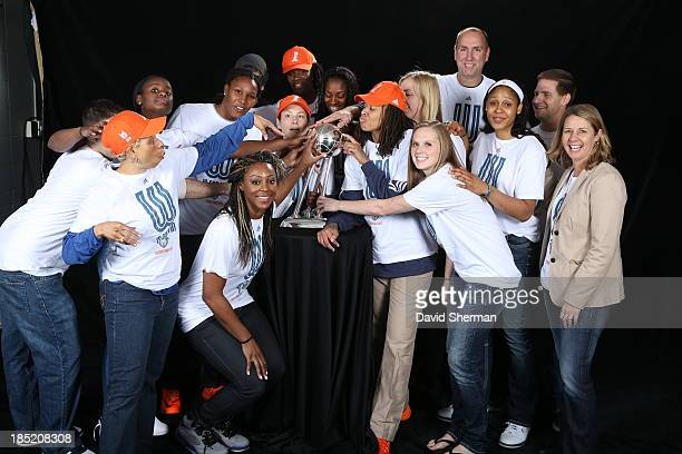 Champion Minnesota Lynx players coaches and trainers overflow the backdrop during a portrait with the 2013 Championship Trophy prior to the...