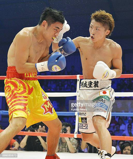 Champion Naoya Inoue delivers a punch to challenger Petchbarngborn Kokietgym of Thailand during the third round of their WBO super flyweight title...