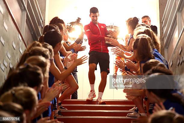 Champion Novak Djokovic of Serbia celebrates with the ball girls following his victory during the Men's Singles final match against Andy Murray of...