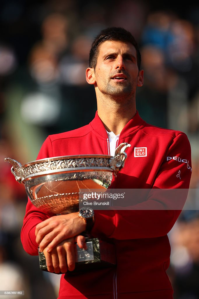 Champion Novak Djokovic of Serbia celebrates with the trophy following his victory during the Men's Singles final match against Andy Murray of Great...