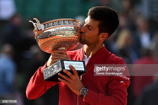 Champion Novak Djokovic of Serbia kisses the trophy following his victory during the Men's Singles final match against Andy Murray of Great Britain...