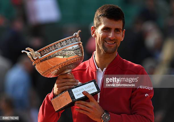 Champion Novak Djokovic of Serbia poses with the trophy following his victory during the Men's Singles final match against Andy Murray of Great...
