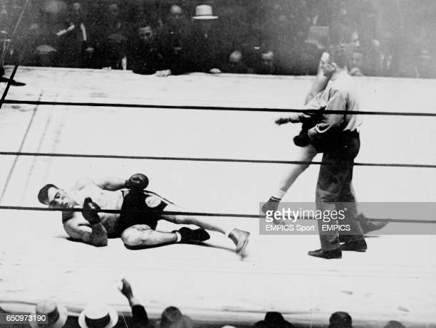 Champion Primo Carnera lies prone on the canvas as challenger Max Baer walks back to his corner having knocked Carnera down for the tenth time in the...