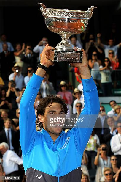 Champion Rafael Nadal of Spain lifts the trophy following his record equalling sixth victory during the men's singles final match between Rafael...