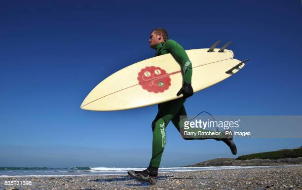 Champion surf boarder Mark 'Egor' Harris from Newquay holds an environmentally friendly surfboard off Fistral Beach Newquay