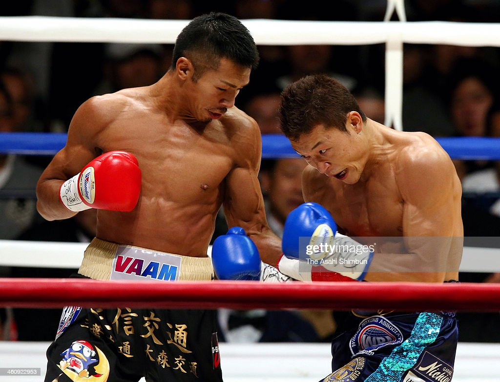 Champion Takashi Uchiyama (L) hits his left on challenger Daiki Kaneko during their WBA Super Featherweight title at Ota-City General Gymnasium on December 31, 2013 in Tokyo, Japan.