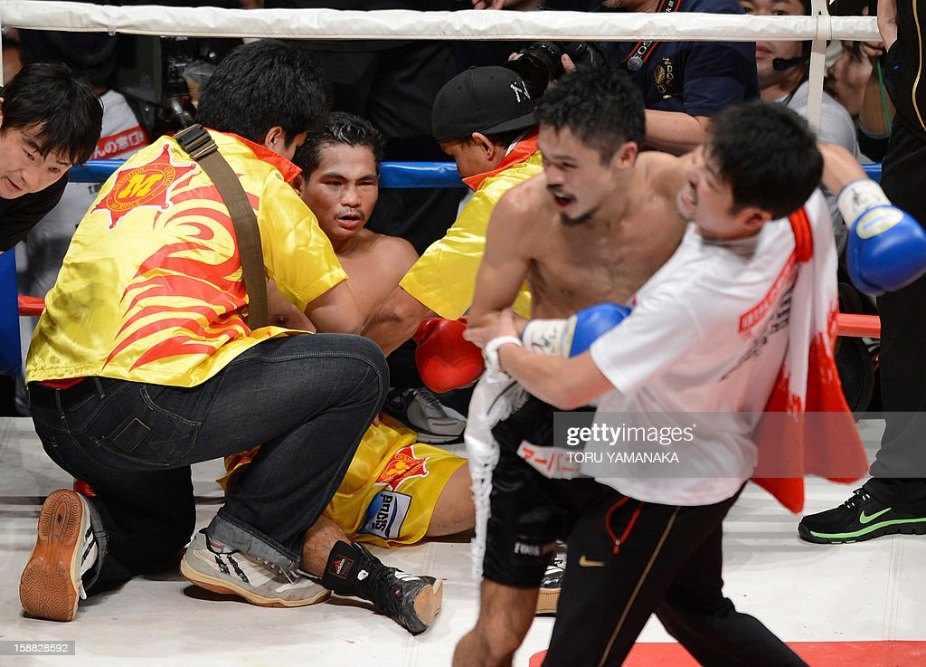 Champion Tepparith Kokietgim (2nd L-facing) is helped by his cornermen after being knocked down by Japanese challenger Kohei Kono (front-2nd R) in the fourth round of their WBA super flyweight title boxing bout in Tokyo on December 31, 2012. The 32-year-old Japanese sent Tepparith onto the ring floor three times in the fourth round to finish off the Thai boxer two minutes, eight seconds into the stanza. AFP PHOTO/Toru YAMANAKA