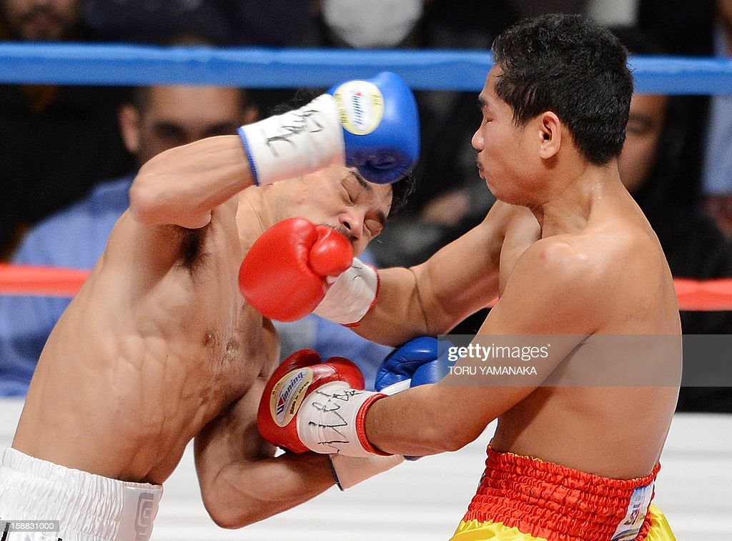 Champion Tepparith Kokietgim (R) of Thailand and Japanese challenger Kohei Kono (L) exchange blows in the second round of their WBA super flyweight title boxing bout in Tokyo on December 31, 2012. The 32-year-old Japanese sent Tepparith onto the ring floor three times in the fourth round to finish off the Thai boxer two minutes, eight seconds into the stanza. AFP PHOTO / Toru YAMANAKA