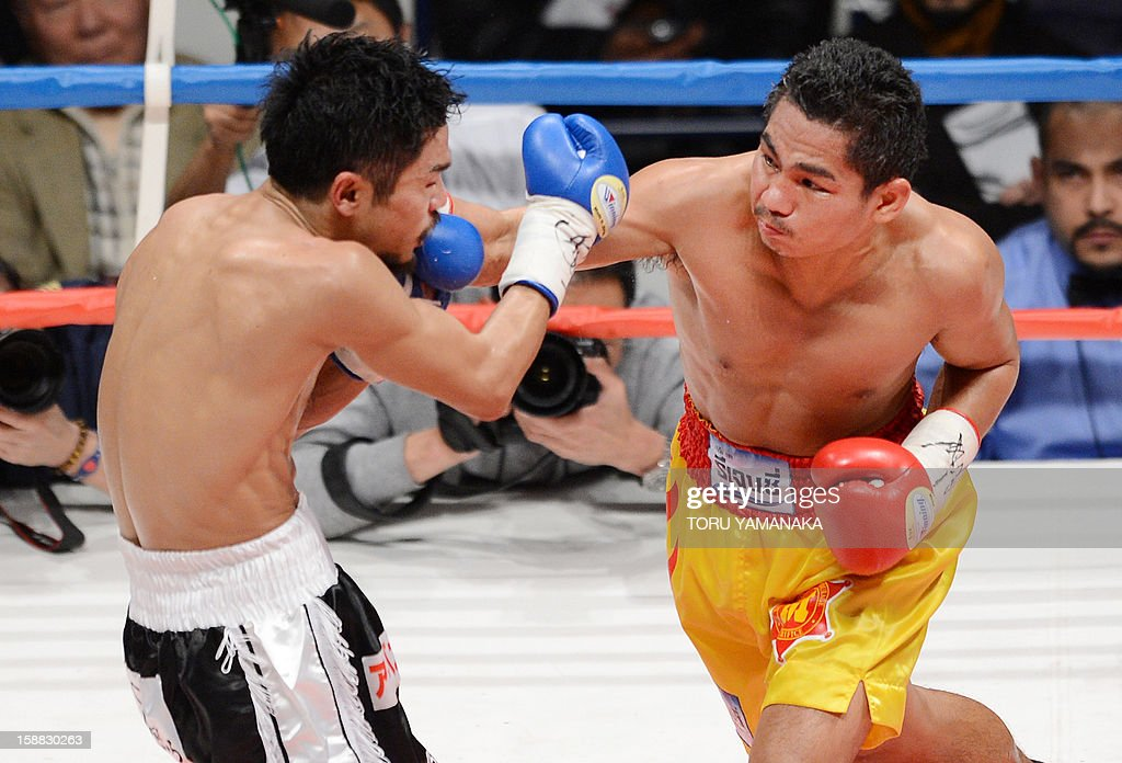 Champion Tepparith Kokietgim (R) of Thailand connects with a right against Japanese challenger Kohei Kono (L) in the third round of their WBA super flyweight title boxing bout in Tokyo on December 31, 2012. The 32-year-old Japanese sent Tepparith onto the ring floor three times in the fourth round to finish off the Thai boxer two minutes, eight seconds into the stanza. AFP PHOTO / Toru YAMANAKA