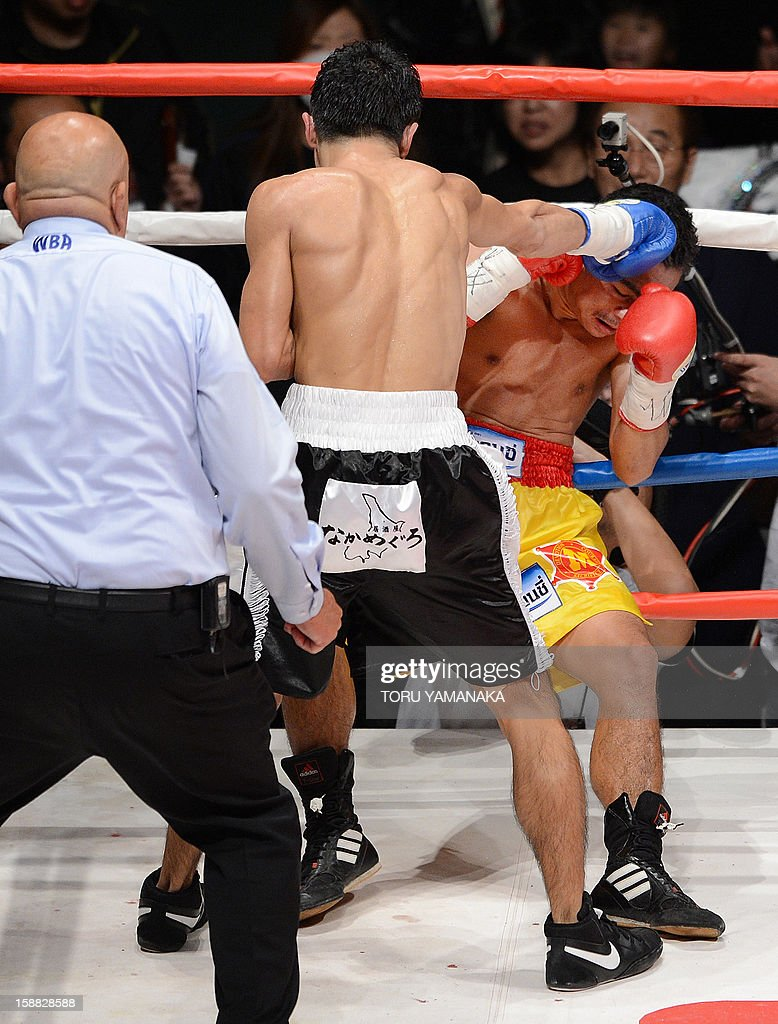 Champion Tepparith Kokietgim (R-facing) receives a right blow as he is knocked down by Japanese challenger Kohei Kono (C-back to camera) in the fourth round of their WBA super flyweight title boxing bout in Tokyo on December 31, 2012. The 32-year-old Japanese sent Tepparith onto the ring floor three times in the fourth round to finish off the Thai boxer two minutes, eight seconds into the stanza. AFP PHOTO / Toru YAMANAKA