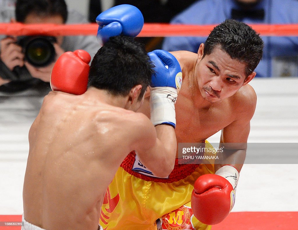 Champion Tepparith Kokietgim (R/facing) sends a right to Japanese challenger Kohei Kono (L) in the third round of their WBA super flyweight title boxing bout in Tokyo on December 31, 2012. The 32-year-old Japanese sent Tepparith onto the ring floor three times in the fourth round to finish off the Thai boxer two minutes, eight seconds into the stanza. AFP PHOTO / Toru YAMANAKA