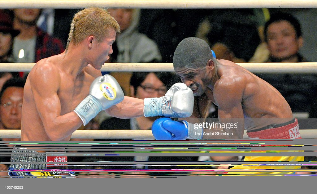 Champion Tomoki Kameda (L) of Japan exchanges punches with Immanuel Naidjala of Namibia during their WBO Bantamweight title bout at the Bodymaker Colosseum on December 3, 2013 in Osaka, Japan.