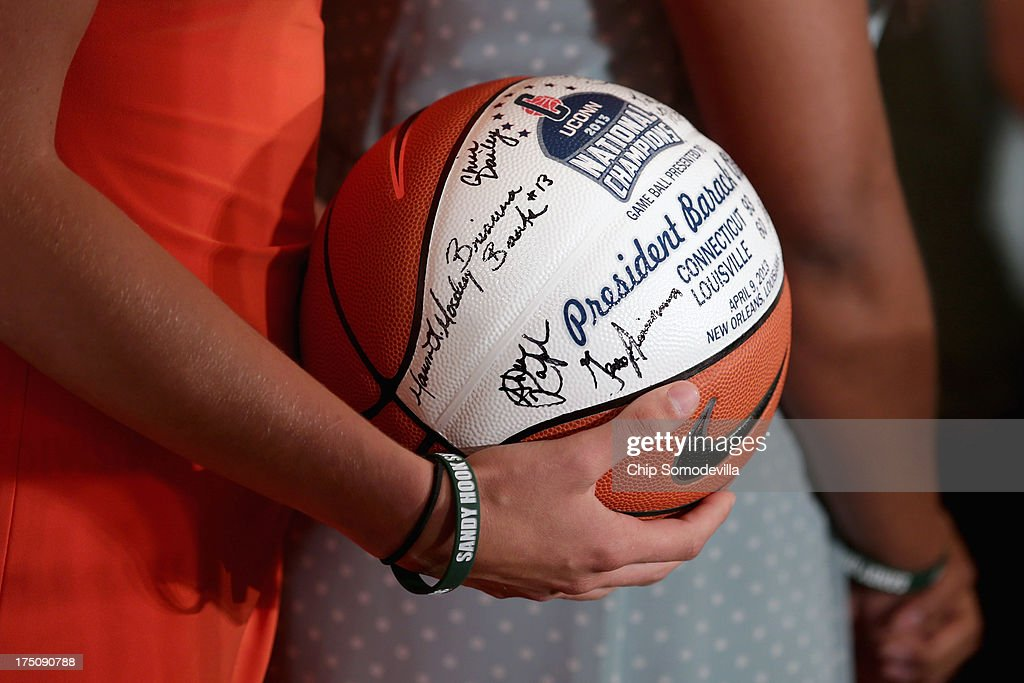 NCAA champion University of Connecticut Huskies Women's basketball players present President Barack Obama with a signed basketball during a ceremony in the East Room of the White House July 31, 2013 in Washington, DC. Obama hosted the team after they defeated the University of Louisville on April 9 to win their eighth national championship.