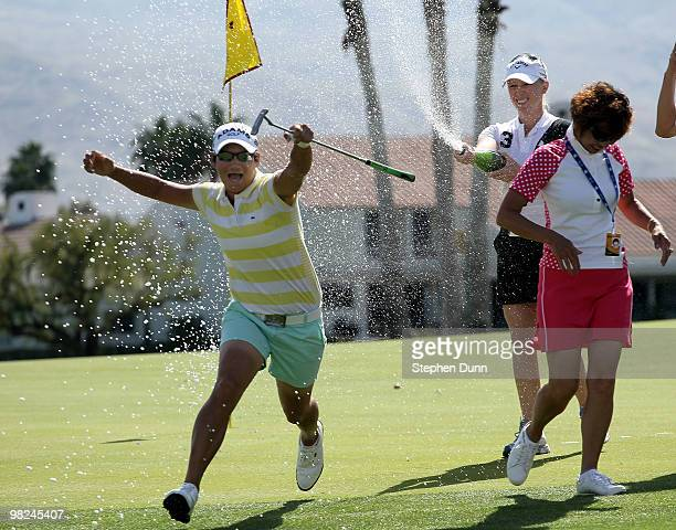 Champion Yani Tseng of Taiwan runs as Morgan Pressel sprays her with Champaign on the 18th green after the final round of the Kraft Nabisco...