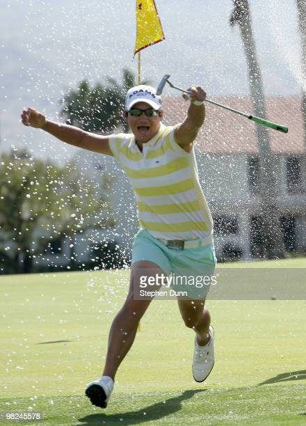 Champion Yani Tseng of Taiwan runs as Morgan Pressel sprays her with champagne on the 18th green after the final round of the Kraft Nabisco...