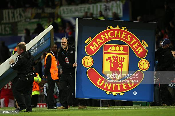Champions League workers hold up a logo of Manchester United during the UEFA Champions League match between Manchester United and Wolfsburg at Old...