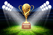 Football winner cup with a golden soccer ball in the light of spotlights on the green grass field of the stadium