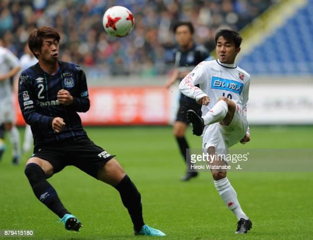 Chanathip Songkrasin of Consadole Sappporo and Genta Miura of Gamba Osaka compete for the ball during the JLeague J1 match between Gamba Osaka and...