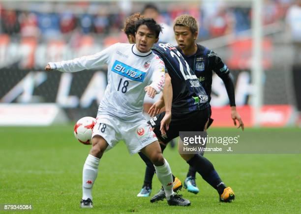 Chanathip Songkrasin of Consadole Sappporo controls the ball under pressure of Oh Jae Suk of Gamba Osaka during the JLeague J1 match between Gamba...