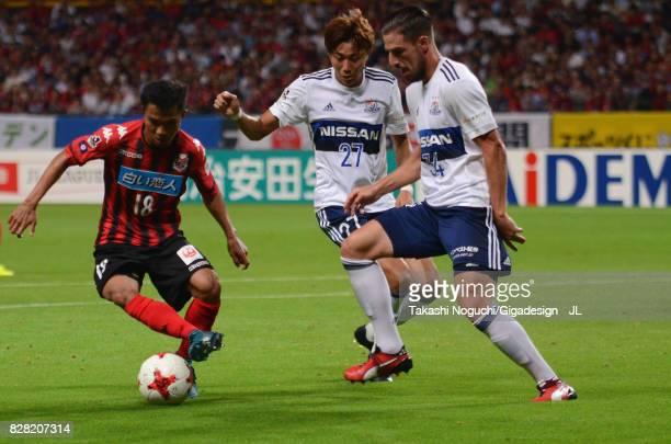 Chanathip Songkrasin of Consadole Sappporo takes on Ken Matsubara and Milos Degenek of Yokohama FMarinos during the JLeague J1 match between...