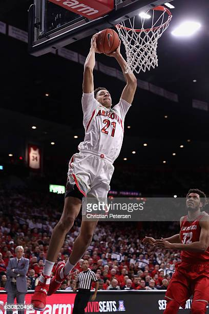 Chance Comanche of the Arizona Wildcats slam dunks the ball ahead of Tim Williams of the New Mexico Lobos during the first half of the college...
