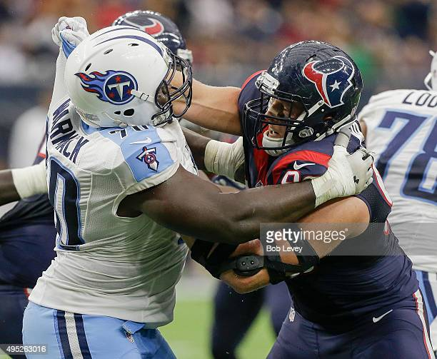 Chance Warmack of the Tennessee Titans and JJ Watt of the Houston Texans lockup at the line at Reliant Park on November 1 2015 in Houston Texas