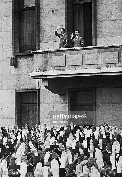 Chancellor Adolf Hitler Propaganda Minister Joseph Goebbels at his side acknowledges cheers of wellwishers who gathered in front of the Chancellory...