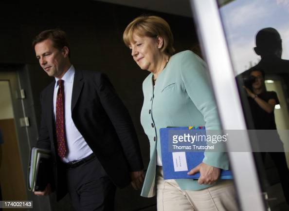 Chancellor Angela Merkel and German government spokesman Steffen Seibert are pictured after a press conference on July 19 2013 in Berlin Germany As...