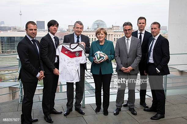 Chancellor Angela Merkel is presented with a ball and a signed shirt from the Geman national football team by DFB president Wolfgang Niersbach and...