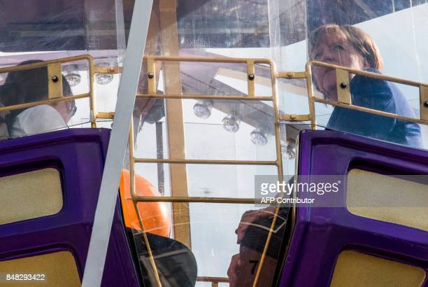 Chancellor Angela Merkel rides a Ferris Wheel at a neighbourhood fair organised by the local branch of the Christian Democratic Union in Stralsund on...
