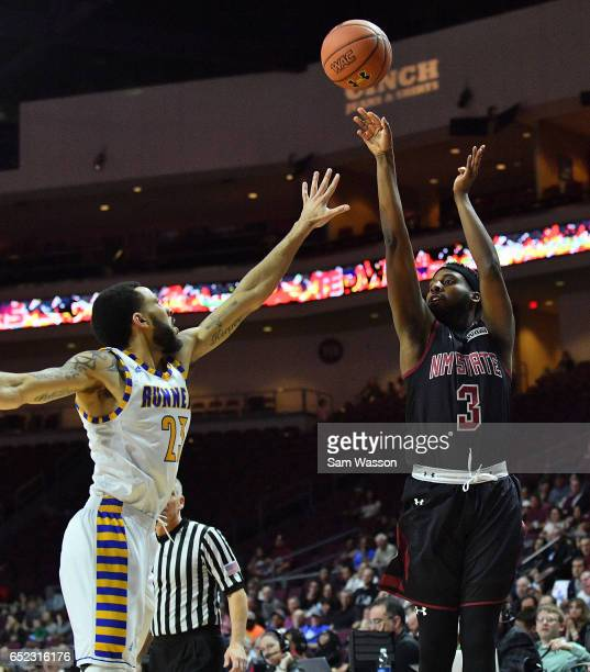 Chancellor Ellis of the New Mexico State Aggies shoots against Damiyne Durham of the Cal State Bakersfield Roadrunners during the championship game...